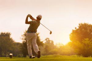 Golfer bei Abschlag ins Abendrot